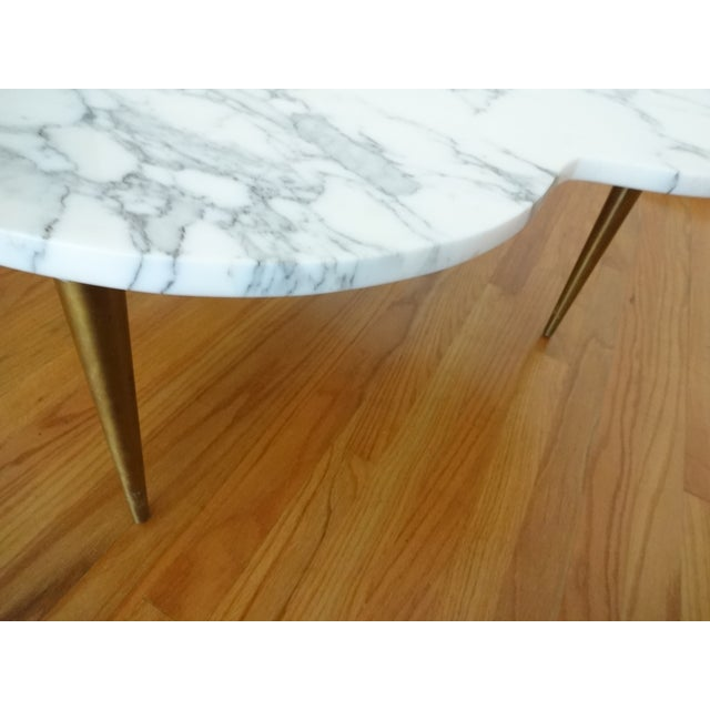 Swanky mid-century marble coffee table. This table's unique trefoil shape, paired with stunning brushed brass tone metal...