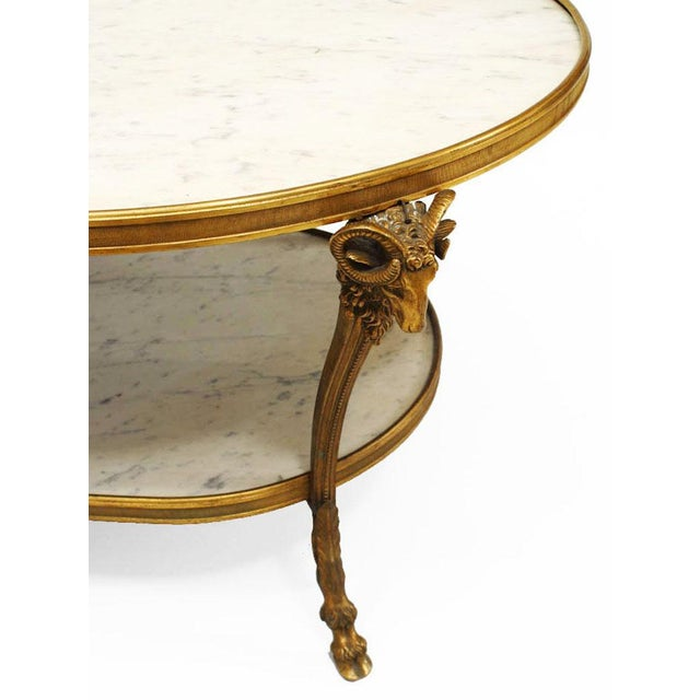 French Louis XVI style (20th century) bronze doré ram head design oval coffee table with white marble top and shelf (as is).