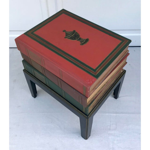 This is a fabulous piece from the mid-century of a stack of books. There are 3 large books on top of a black and gold...