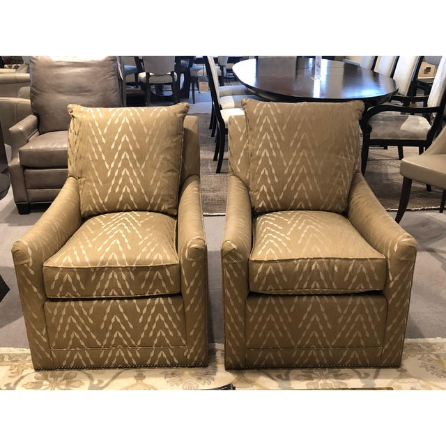 Petite in width tall in height upholstered to the base recessed swivel caster mechanism covered in a khaki fabric with a...