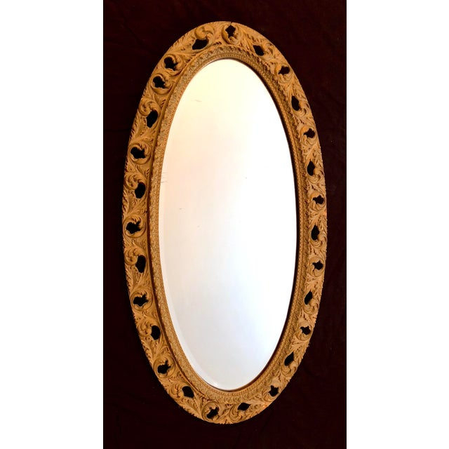 An elegant extended oval wall mirror with ornate wood carvings and aged gold / Gilt finish. Set up to hang vertically but...