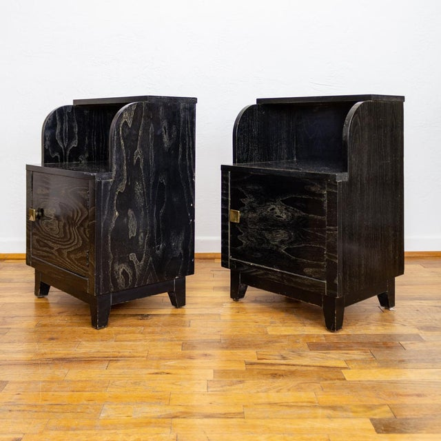 Mid Century two tiered nightstands feature a black furniture stain that reveals the natural woodgrain, emphasized with a...