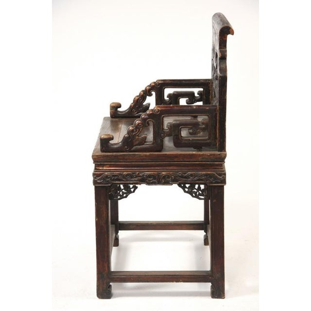 A powerful and dramatic pair of Chinese carved walnut wood (hetao mu) arm chairs. The back features two facing stylized...