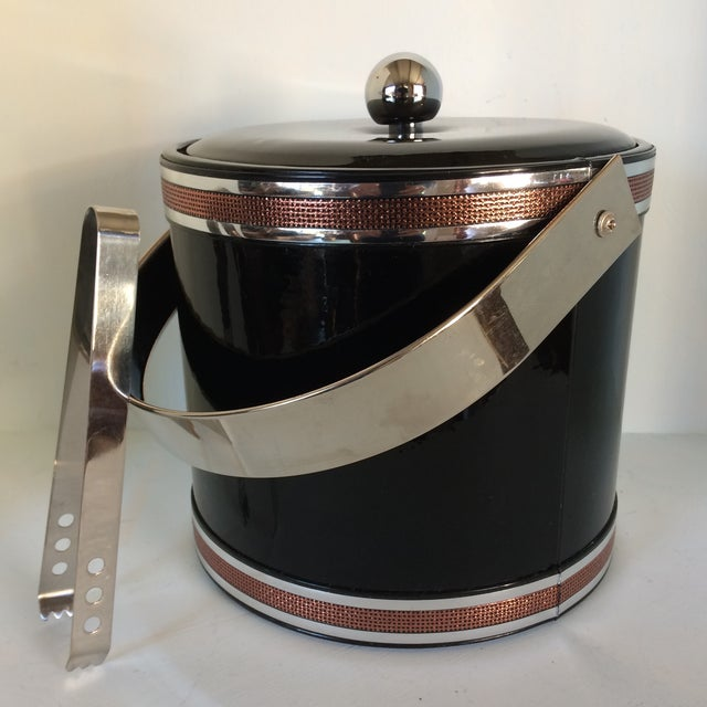 Nice clean stylish Georges Briard black vinyl ice bucket with chrome handle, knob, and ice tongs. Signature is on the...