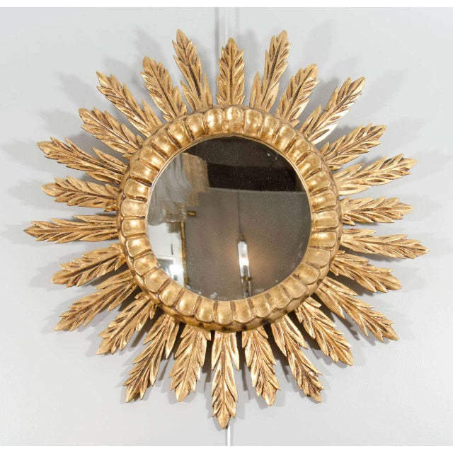 A lovely sunburst mirror with alternating sized carved rays surrounding moulded centre, France, circa 1970.