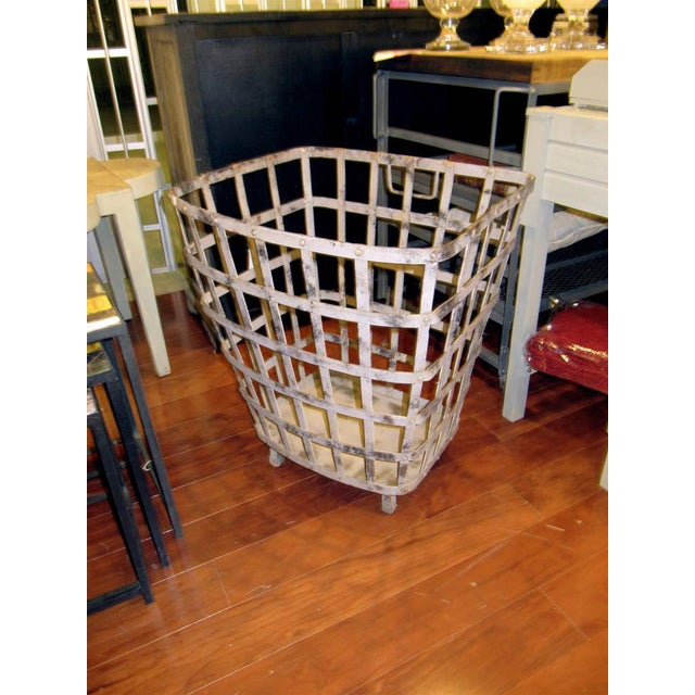Industrial iron basket with worn painted finish.
