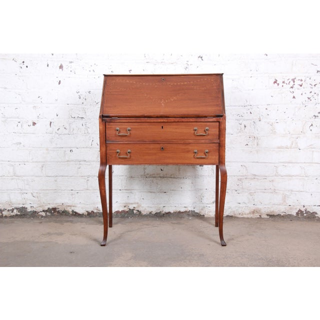 A gorgeous Louis XV Style drop-front secretary desk. The desk features beautiful mahogany wood grain, with floral...