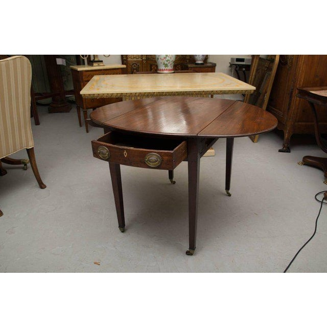 This is an English solid mahogany oval Pembroke table. A central drawer is below the top overhang. The table rests on...