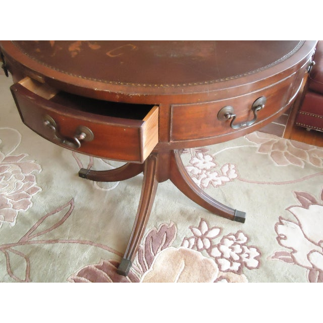This is a vintage federal style game table from the mid 20th century. The piece features carved wood, a leather top, and...