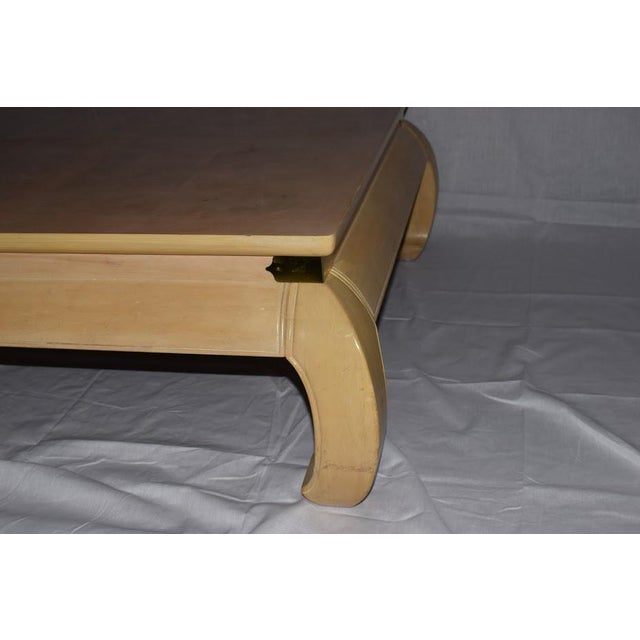This Asian coffee table has a light tan color finish, yet the wood is very heavy and solid. It also features brass details...