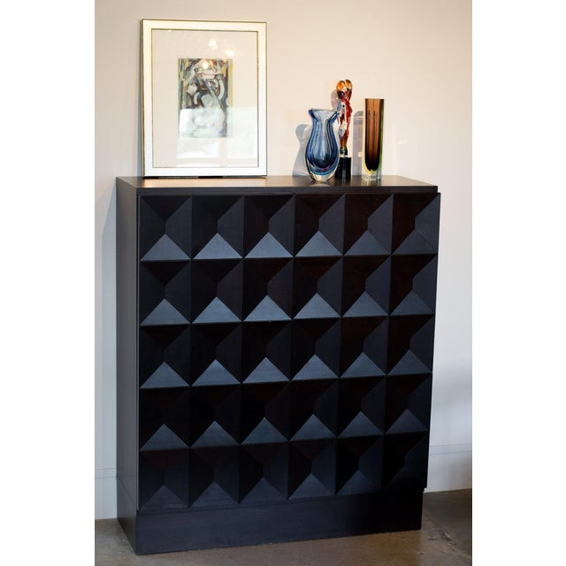 Midcentury dry bar or cabinet with rich chocolate stain over geometric patterned doors. Brutalist styling characteristic...