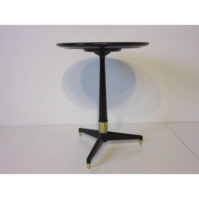 A dark and rich ebony finished side table with tri-pod base, brushed brass details and round top with raised lip. The...