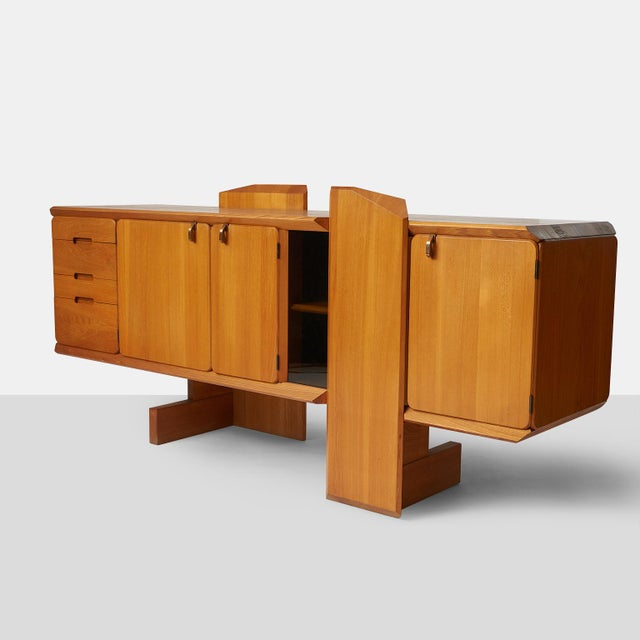 A credenza in elmwood model #R28 designed by Pierre Chapo. The cabinet features 4 drawers, three doors in different sizes...