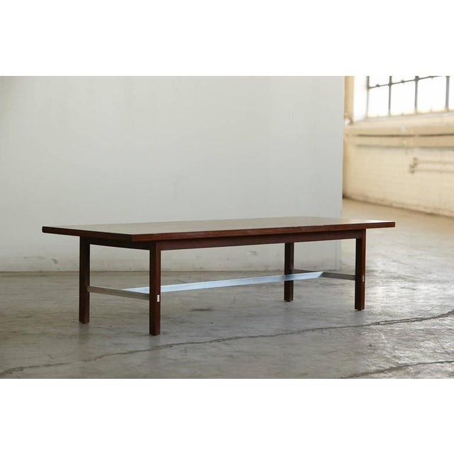 Beautiful, low, rectangular coffee table in walnut and thin strips of aluminum, who cross brace into the walnut legs for...