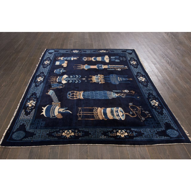 A antique hand-knotted Chinese rug with a pictorial design on a blue field. This rug has magnificent detailing and would...