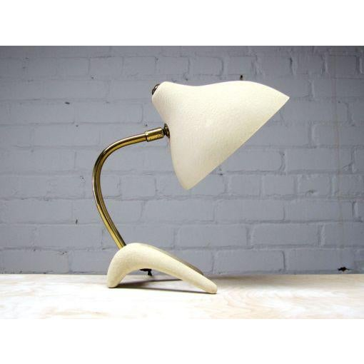 Elegant petite cream colored table lamp designed by Louis Kalff for Philips, the conical shade is held by a curved brass...