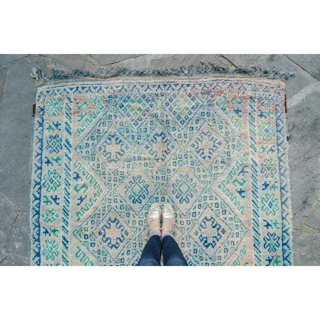 A delightful Moroccan rug with diamonds, steps, and cross motifs throughout featuring colors such as teal, blue, blush,...