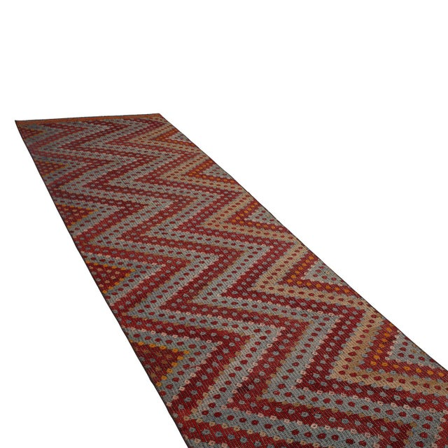 Hand woven in Turkey originating between 1950-1960, this vintage mid-century wool kilim rug enjoys a meticulous play of...