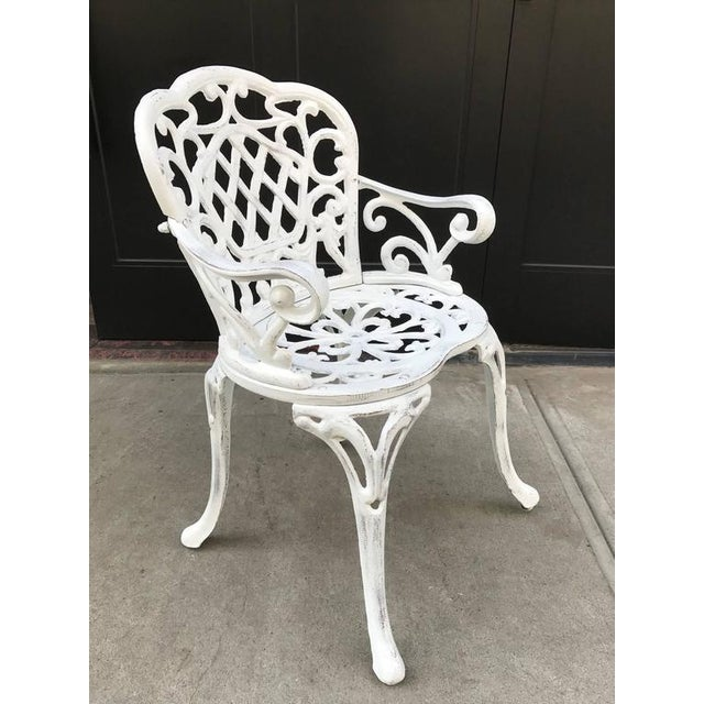 Set of four, early cast iron garden armchairs. Painted white finish with a decorative pattern.