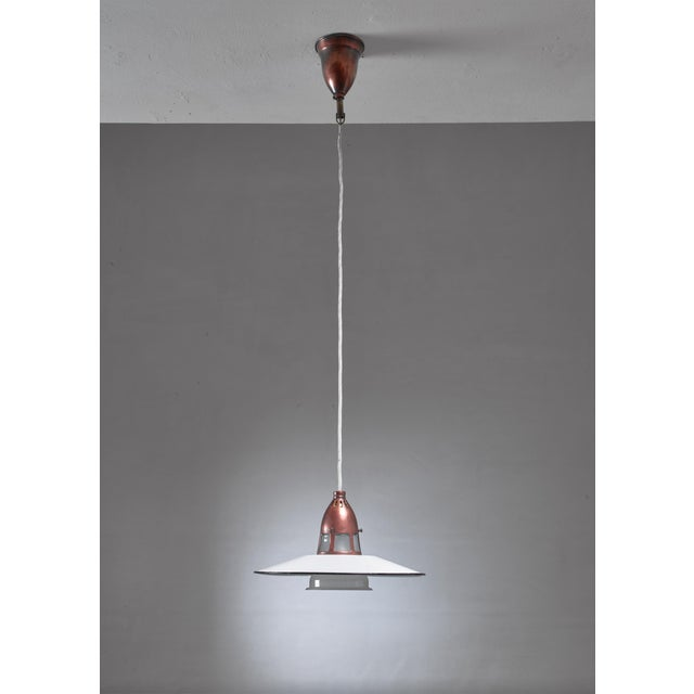 A Danish copper and glass pendant by Lyfa. The lamp has a white enameled metal shade and a frosted glass diffuser in a...