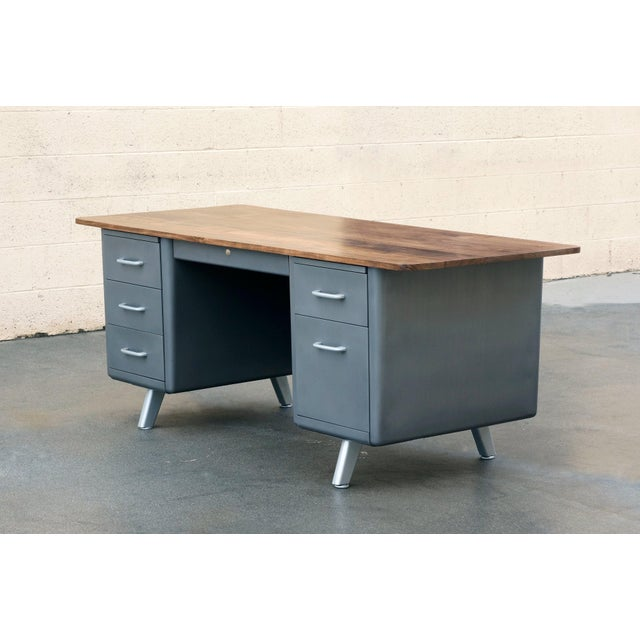 Mid-century steel tanker desk refinished with a twist. This beauty features an oversized solid walnut top with radius...