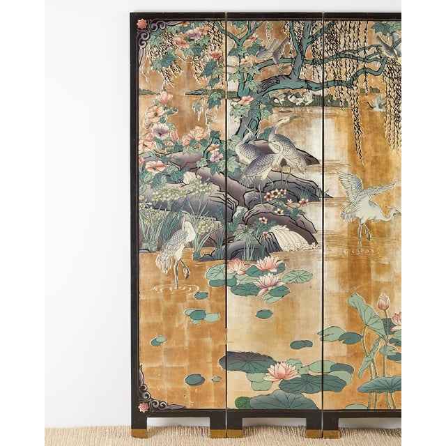 Stunning Chinese export six-panel Coromandel screen featuring a water landscape with cranes on a dramatic gilt background....