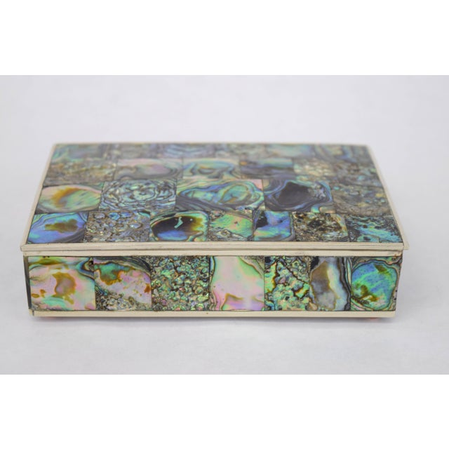 Beautiful Mexican silver plate box cased in abalone by Alpaca. Hinged lid reveals walnut interior for storage. Stamped to...