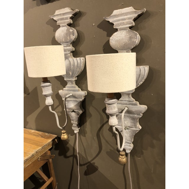 Pair of painted wood sconces in hues of gray with cream linen half shades.Gold wood adornments hanging from arm.Cloth wire...