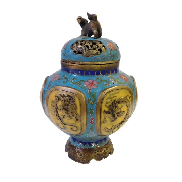This is a round fat body incense ding burner made of metal and covered with blue & yellow enamel color. There are floral...