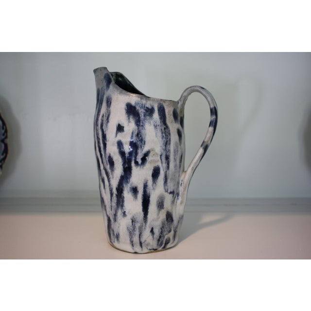 This vintage handmade stoneware pitcher is quite heavy and is painted in abstract blue strokes on white ground with deep...