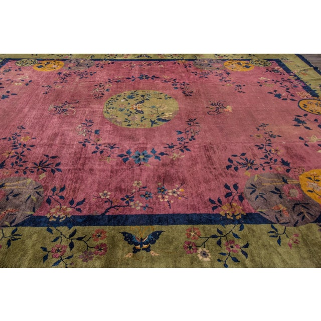 A Chinese Art Deco rug with a green and navy border and pink field. The term Art Deco refers to the style launched at the...