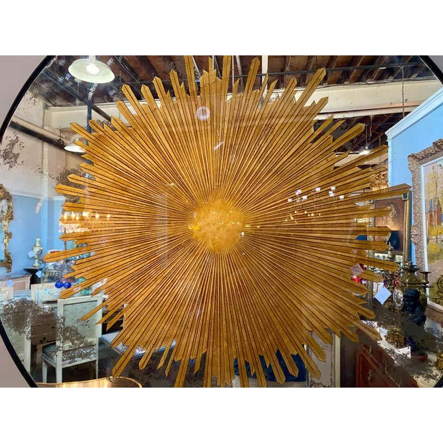 Pair of monumental carved gilt gold and silver glass sunburst wall mirrors or table tops. These spectacular finely...