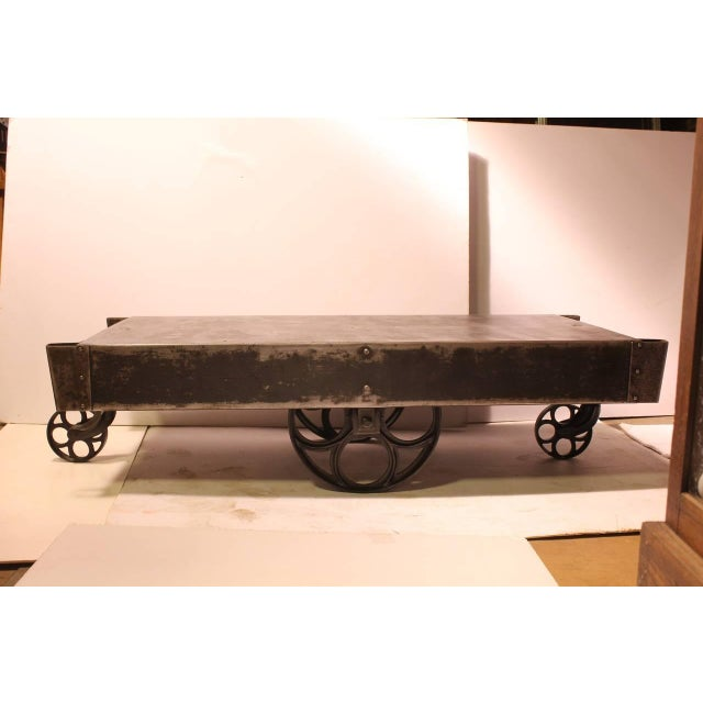 Stylish antique American industrial steel cart coffee table with cast iron wheels. Newly refinished. More available.