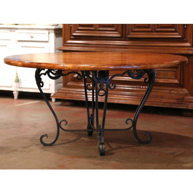 Crafted in the USA circa 1990, the elegant table stands on forged cabriole legs ending with scrolled feet over a curved...