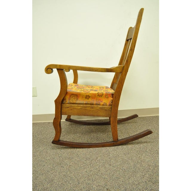 Item: Charming Vintage Solid Oak Rocking Chair. The chair is lightly carved with scrolled arms, slat back, and overall...