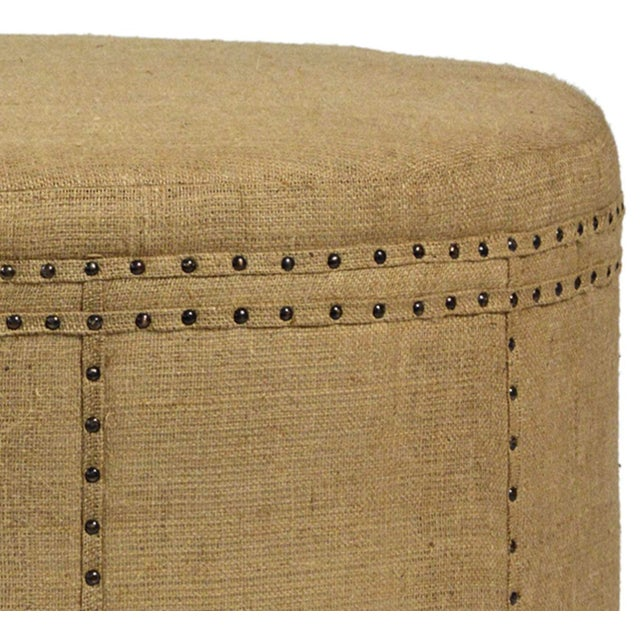 Beautiful hand crafted round jute upholstered ottoman with antiqued nail head detail. Hardwood frame. Each may vary...
