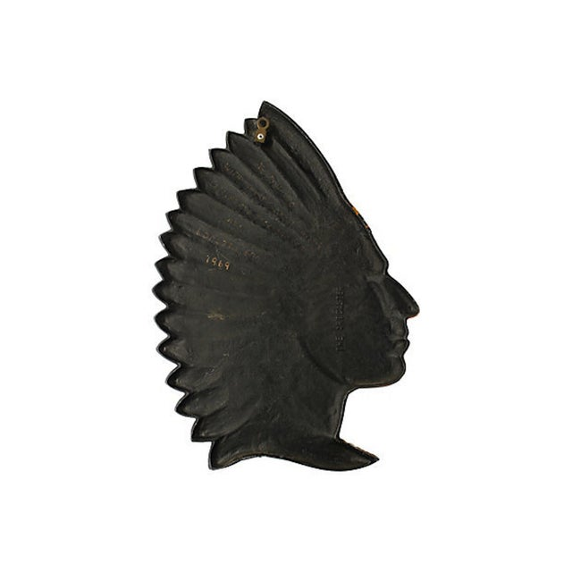 "A 1960s metal relief hand-painted chief profile marked ""The Artcaster"" on underside. Has brass hanger on reverse. Age..."