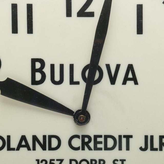 An electric wall clock by Bulova. The metal, silver metallic case features a white dial with black Arabic numerals and...