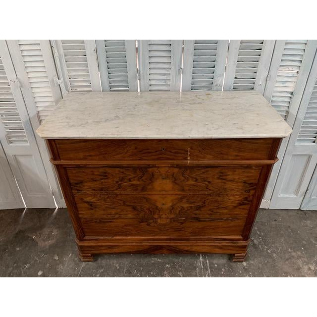 Beautiful French Louis Philippe commode made of solid walnut and topped with a thick white Carrara marble slab. Resting...