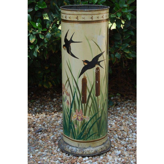Unusual and charming hand-painted umbrella stand depicting rice birds, cattails and wild iris on a cream-colored...