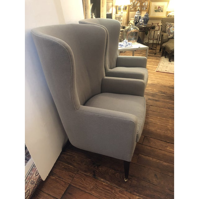 Absolutely sublime pair of Baker barrel back wing chairs upholstered in Robert Allen soft refined grey flannel. The legs...