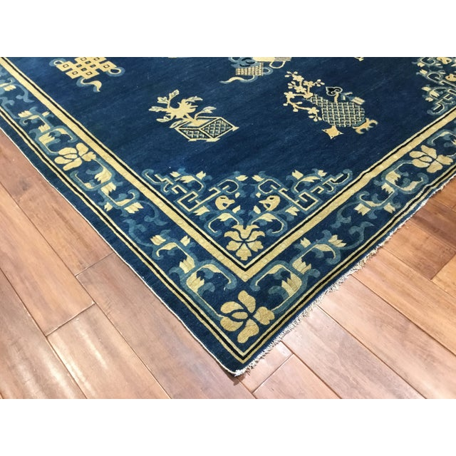 Blue and white Peking carpet from early 20th century patterned with Chinese symbols