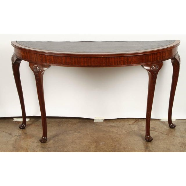 A very shallow 19th Century English mahogany demilune table, with leather inset top.