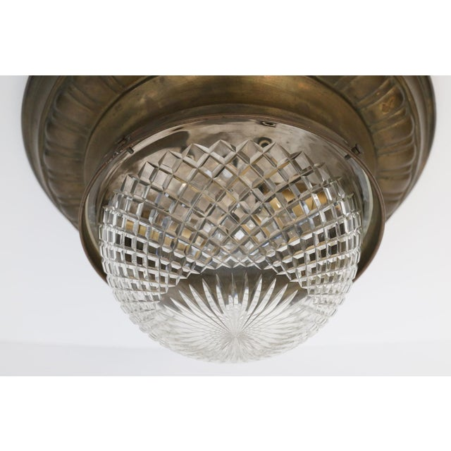 Repousse flush mount light: brass fixture circled by repousse decoration and finished with unusually deep cut-glass dome....