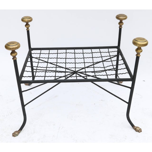 Black metal bench or stool with decorative brass finials and claw feet.