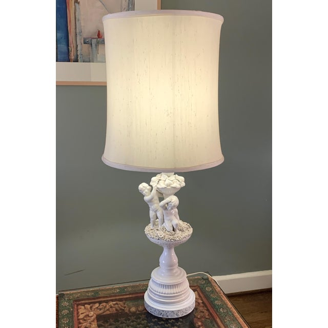 """Vintage Porcelain Cherub Table Lamp with Floral Details and White Lampshade. 41"""" tall x 12"""" wide diameter. No designer..."""