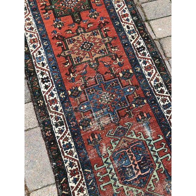 Vintage Karajeh runner with a distressed, low pile and all-over wear. Tribal diamond pattern with a deep rust field. Other...