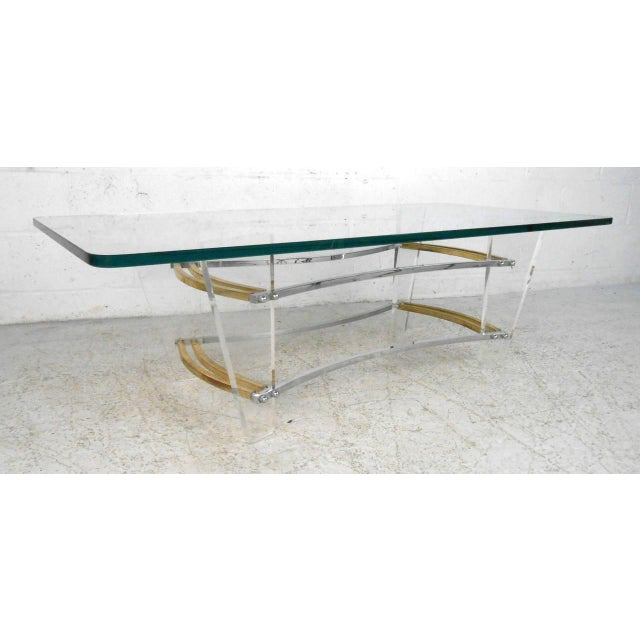 This beautiful lucite and brass cocktail table adds subtle modern style to any room. Sturdy base and thick glass top make...