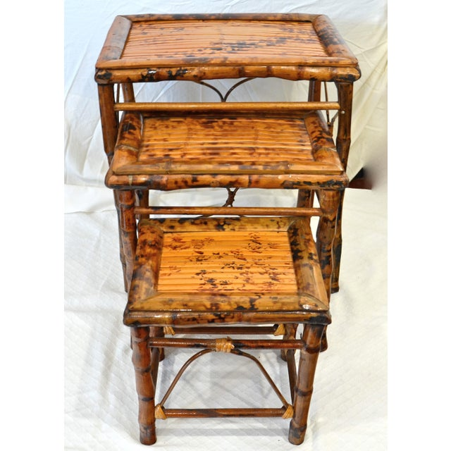 A set of three vintage tortoise or tiger finish bamboo nesting tables with slat tops and lashed side accents. These are a...