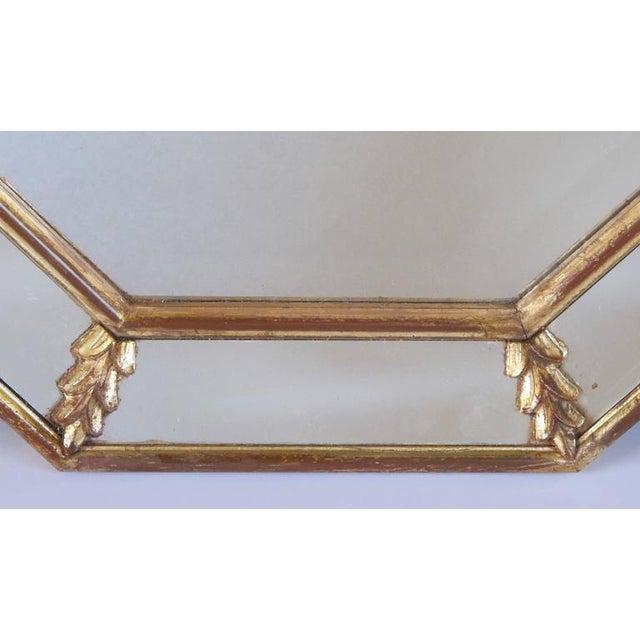 A shimmering French 1960s giltwood octagonal mirror with foliate elements; the octagonal beveled plate within a mirrored...
